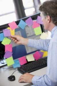 Businessman in office at monitor with notes on it